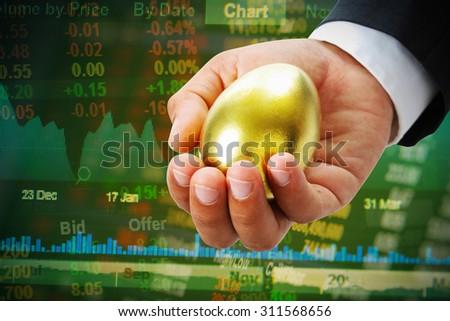 businessman hold golden egg on stock market  - stock photo