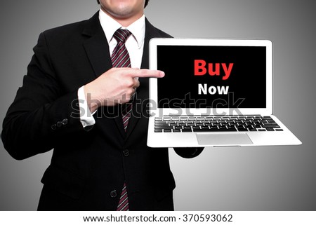"businessman hold laptop and finger point on screen show text "" Buy now """