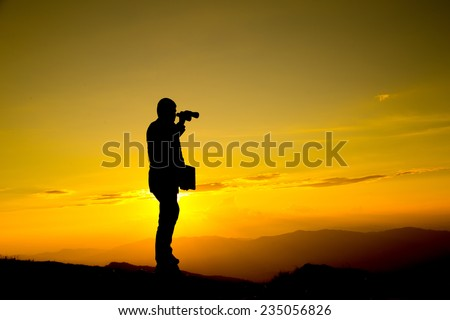 Businessman hold laptop and watch binoculars for his vision on the high mountai - stock photo