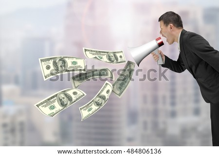 Businessman hold megaphone with dollar bills spraying out, on city buildings background.