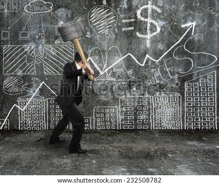 Businessman hold sledgehammer to crack hand-drawn doodles concrete wall background - stock photo