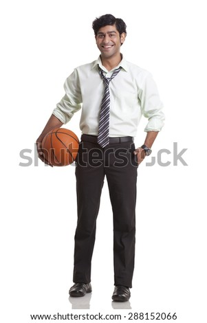 Businessman holding a basketball - stock photo