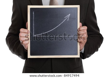 Businessman holding a blackboard with a graph showing a positive trend with space for message - stock photo