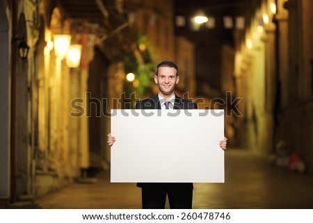 Businessman holding a blank panel in a city street