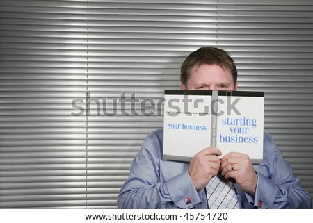 Businessman holding a book titled Starting Your Business,