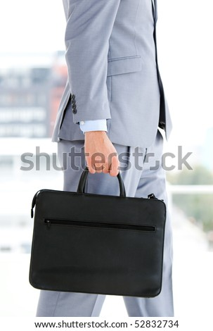 Businessman holding a briefcase in the office