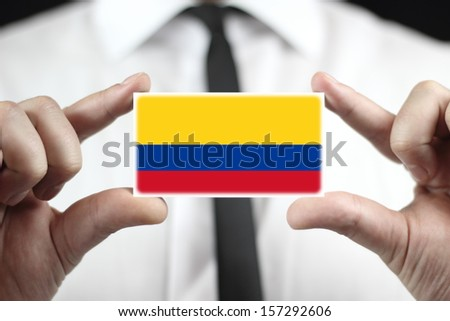 Businessman holding a business card with Colombia Flag - stock photo
