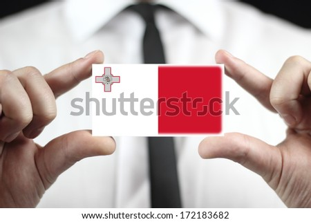 Businessman holding a business card with Malta Flag - stock photo