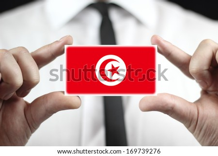 Businessman holding a business card with Tunisia Flag - stock photo