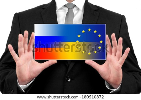Businessman holding a business card with Ukraine, EU and Russia Flag - stock photo