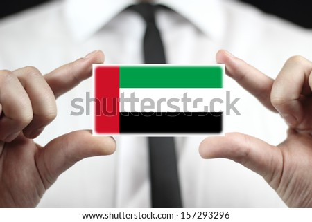 Businessman holding a business card with United Arab Emirates Flag - stock photo