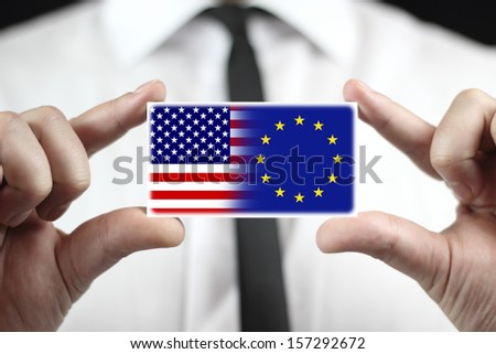 Businessman holding a business card with USA and EU Flag - stock photo