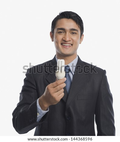 Businessman holding a CFL bulb - stock photo