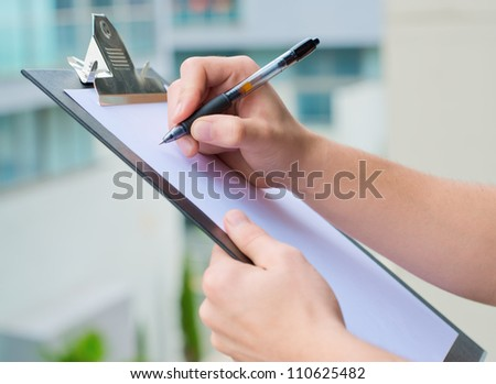 Businessman Holding A Clipboard And Writing, Out Door