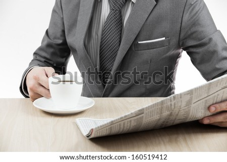 Businessman holding a cup of coffee and reading a newspaper on table - stock photo