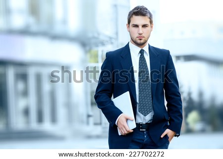 Businessman holding a digital tablet computer, standing in front of his office. - stock photo