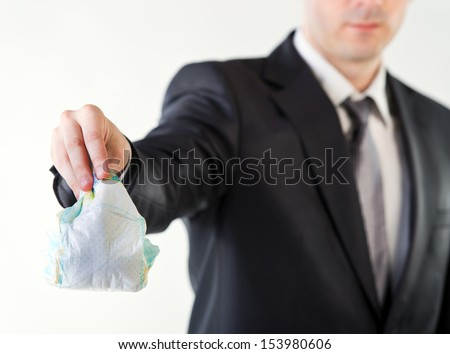 Businessman holding a dirty diaper