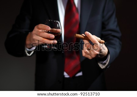 Businessman holding a glass of cognac and cigar