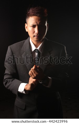 businessman holding a gun with a black background - stock photo