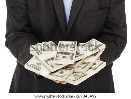 Businessman holding a heap of money in his hands - stock photo