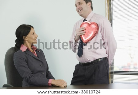 Businessman holding a heart shaped gift in front of a businesswoman - stock photo