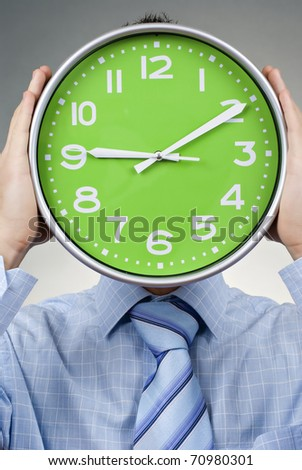 Businessman holding a hour on grey background - stock photo