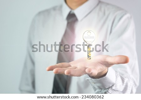 Businessman holding a key with the word success on it - stock photo