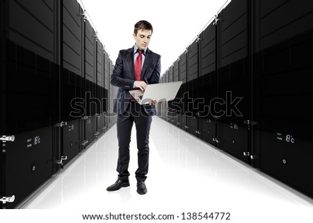 businessman holding a laptop with servers in the background - stock photo