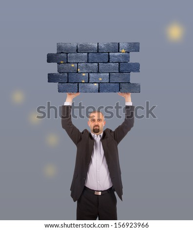 Businessman holding a large piece of a brick wall, flag of Alaska, isolated on national flag - stock photo