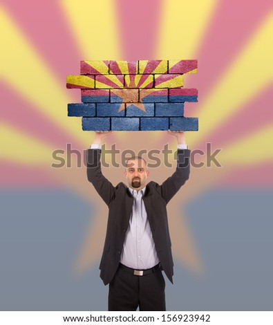 Businessman holding a large piece of a brick wall, flag of Arizona, isolated on national flag - stock photo
