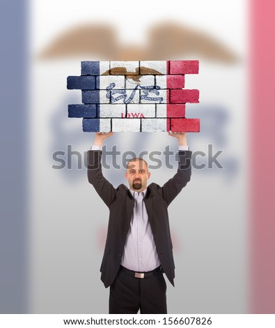 Businessman holding a large piece of a brick wall, flag of Iowa, isolated on national flag - stock photo