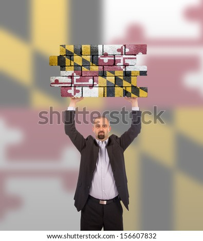 Businessman holding a large piece of a brick wall, flag of Maryland, isolated on national flag - stock photo