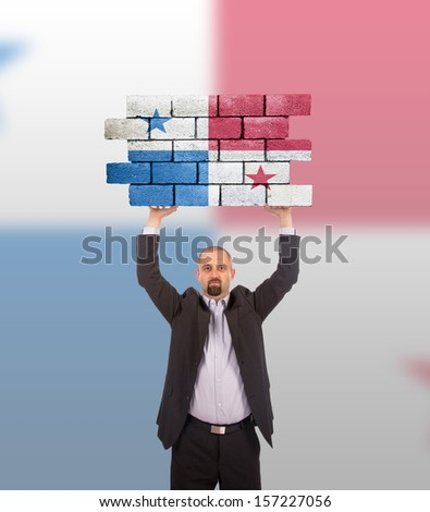 Businessman holding a large piece of a brick wall, flag of Panama, isolated on national flag - stock photo