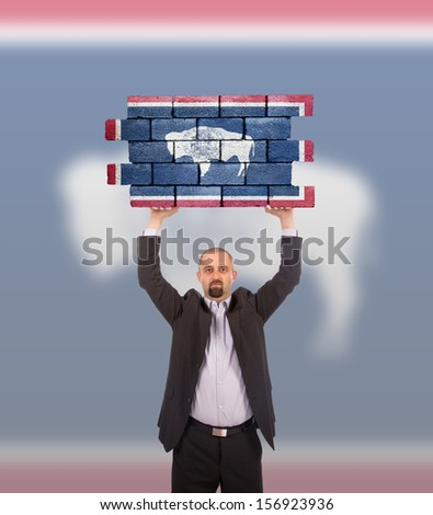 Businessman holding a large piece of a brick wall, flag of Wyoming, isolated on national flag - stock photo