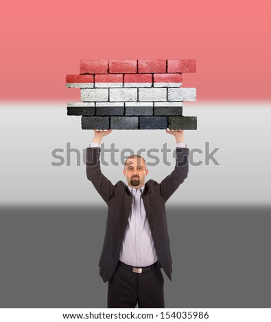 Businessman holding a large piece of a brick wall, flag of Yemen, isolated on national flag - stock photo