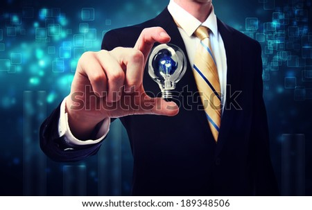 Businessman holding a light bulb over blue shiny background - stock photo