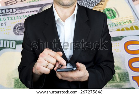 businessman holding a mobile phone, the background of money - stock photo