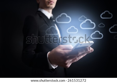 businessman holding a mobile phone with cloud icons on virtual screen. Internet concept. business concept. - stock photo