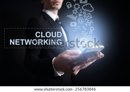 businessman holding a mobile phone with cloud networking text and applications icons. Internet concept. - stock photo