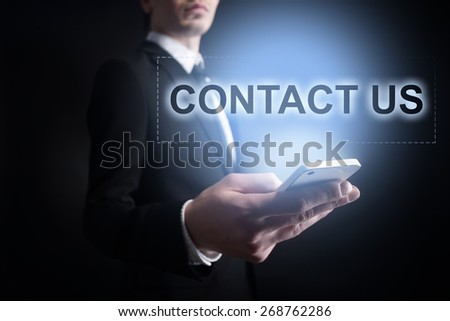 Businessman holding a mobile phone with contact us text on virtual screen. Internet concept. Business concept. - stock photo