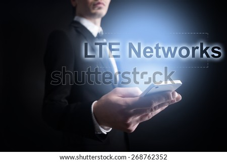 Businessman holding a mobile phone with LTE networks text on virtual screen. Internet concept. Business concept. - stock photo