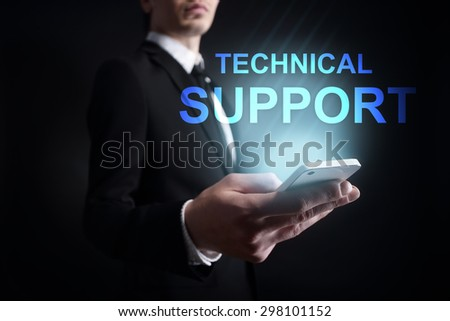 "Businessman holding a mobile phone with ""Technical support"" text on virtual screen. Internet concept. Business concept. - stock photo"