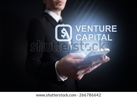 Businessman holding a mobile phone with venture capital text on virtual screen. Internet concept. Business concept.