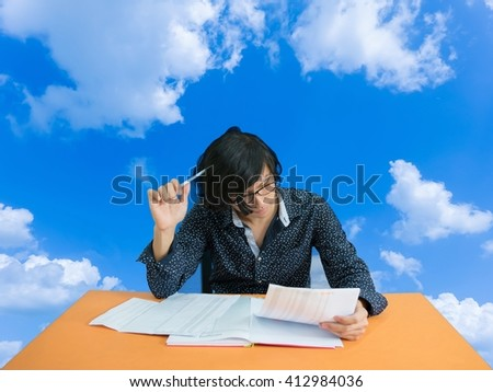 Businessman holding a pen and thinking - Brainstorming concept, generating ideas, Conceptual image. - sky clouds background with copy space. - stock photo
