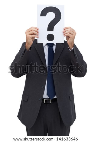 Businessman holding a question mark paper in front of his face on white background - stock photo