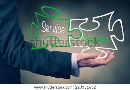 Businessman holding a Service Guarantee concept puzzle.  - stock photo
