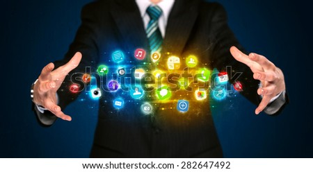 Businessman holding a shining app icon cloud in front of his body - stock photo