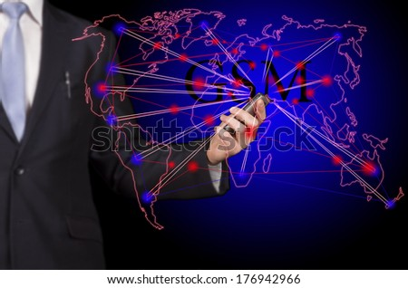 "businessman holding a smartphone in hand, linking business and social networks with the inscription ""GSM"" - stock photo"