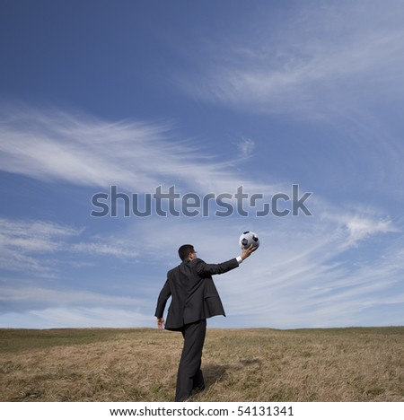 Businessman holding a soccer ball up in the air in outdoor - stock photo