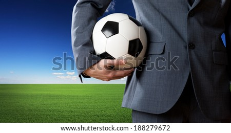 Businessman holding a soccer ball with blue sky and green meadow on background. - stock photo
